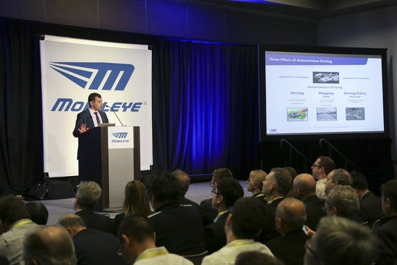 Amnon Shashua at a podium, next to a slide outlining Mobileye's self-driving effort