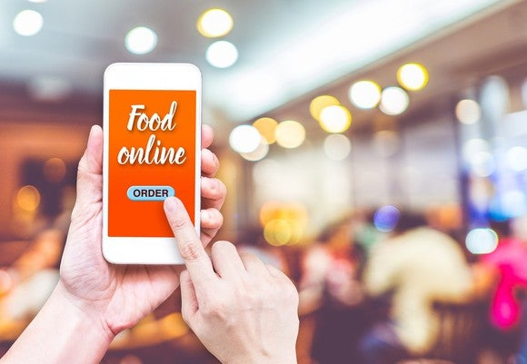 Person using smartphone to order food online.