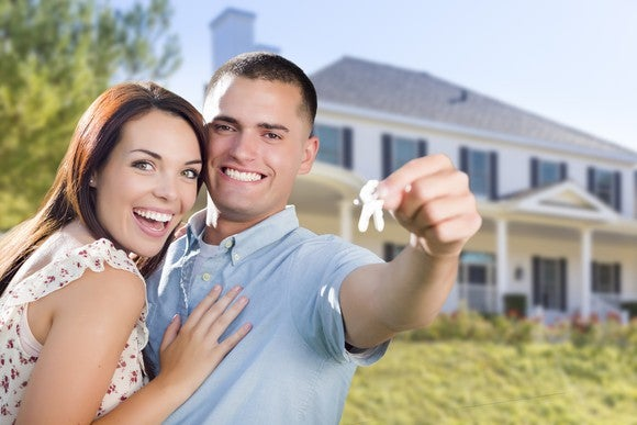Younger couple holding the keys to their first house.