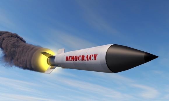 "Rocket labeled ""Democracy"" blazing a trail of smoke across the sky."