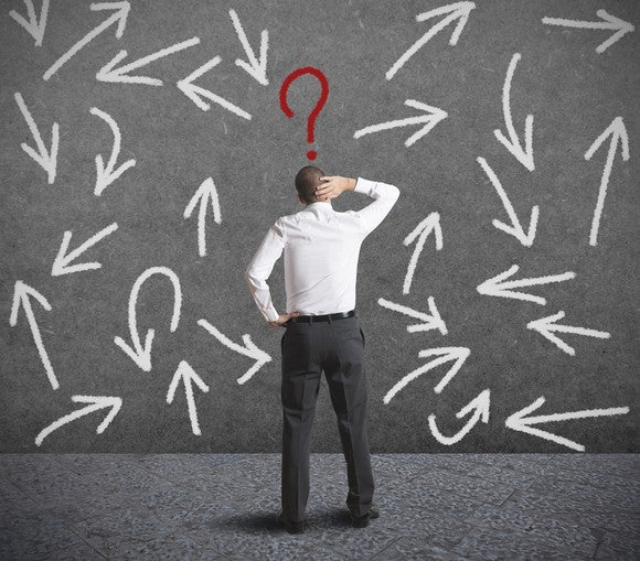 A man facing a wall with arrows pointing in various directions and a question mark over his head.