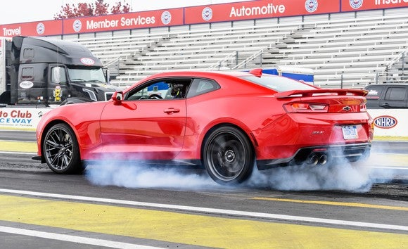 A red Chevrolet Camaro burning rubber on a drag strip.