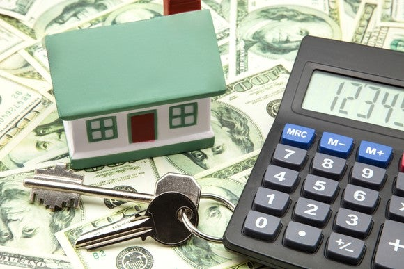 House with calculator, keys, and money.
