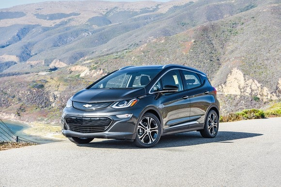 A black Chevy Bolt with mountains in the background.