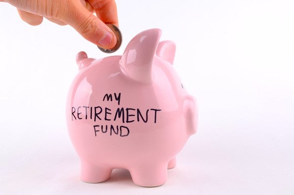 "Person putting money into a pink piggy bank labeled ""My Retirement Fund"""