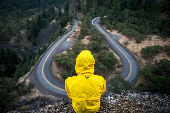 Figure wearing a raincoat starting at winding road