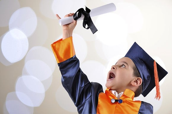 A child in a cap and gown holding up and admiring a diploma.