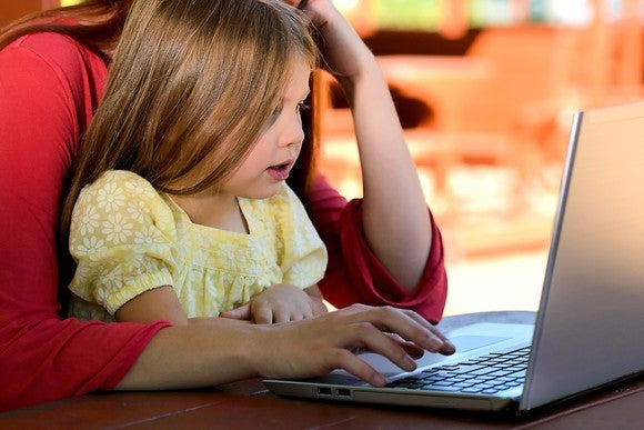 Child on parent's lap in front of laptop.