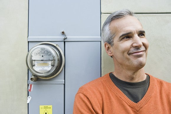 Man smiling, standing next to electricity meter on his home.