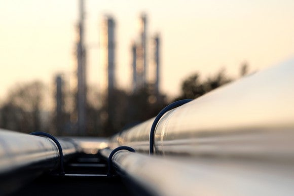 Pipelines in foreground terminating at a refinery in background