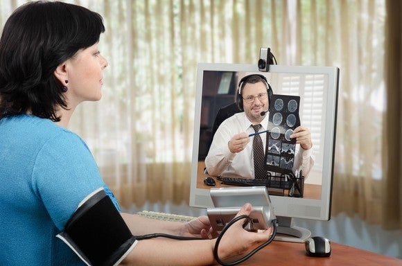 Female patient taking blood pressure in videoconference with doctor