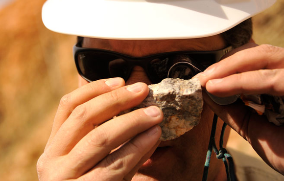 An image of a Hecla Mining employee examining a rock.