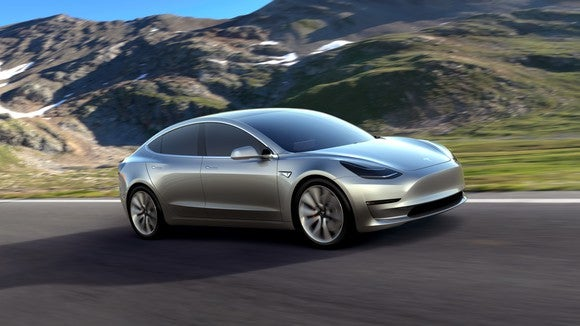 A silver Tesla Model 3 concept car on a mountain road