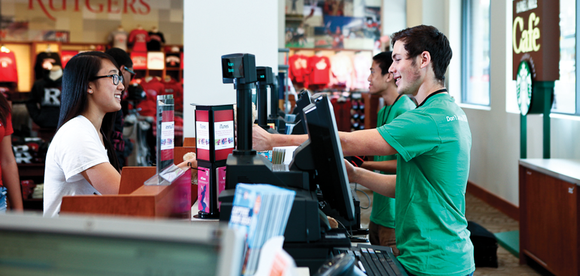 Customer at the counter of a Barnes & Noble Education store with clerks.