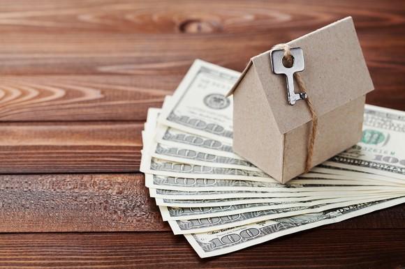 Cardboard house on top of $100 bills.