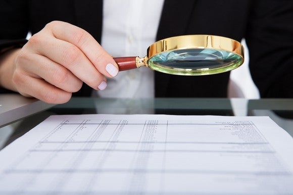 A businesswoman holds a magnifying glass over a financial document.