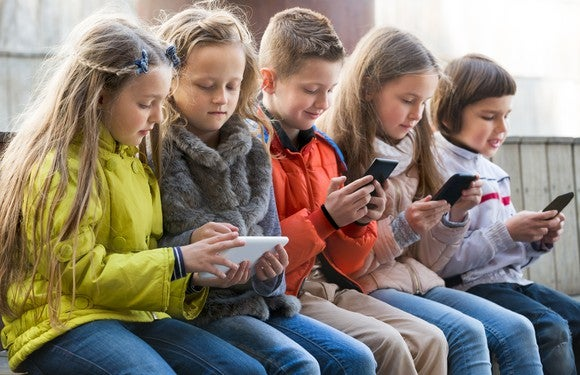 Group of kids all using mobile devices