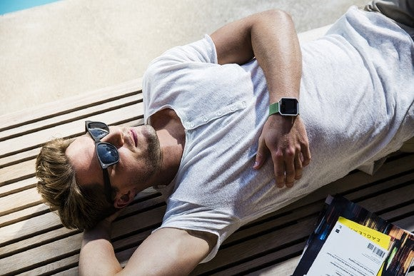 Fit bearded man with sunglasses relaxing with Fitbit Blaze on his wrist.
