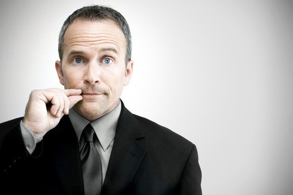 Businessman with hands in from of lips indicating secrecy/quiet.
