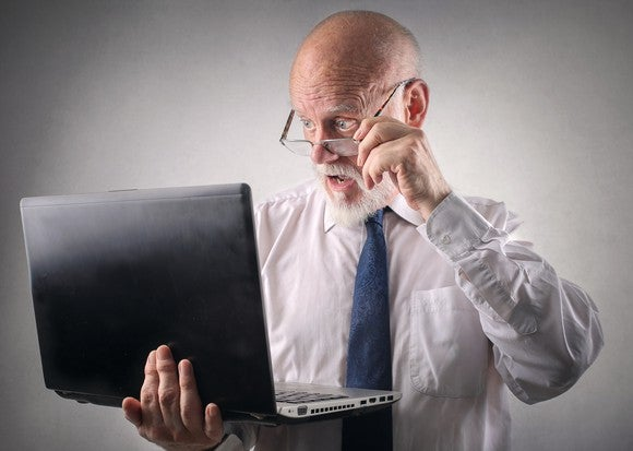 Man appearing to be shocked at something on a laptop.