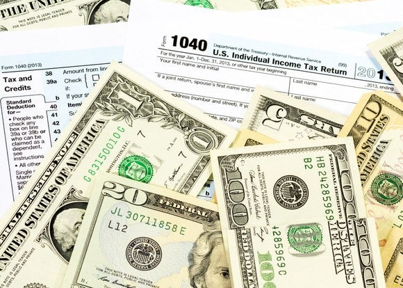 IRS form 1040 with money on top of it.