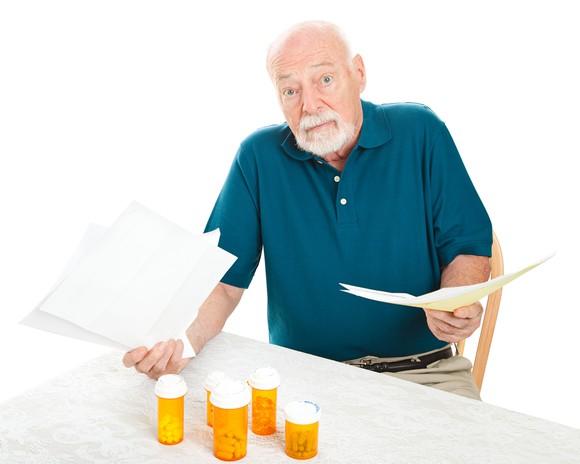Senior man annoyed by high prescription drug prices.