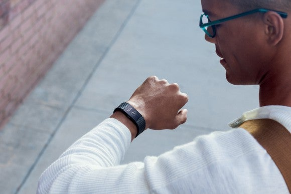 Man in glasses looking at his Fitbit Charge 2 on his wrist.