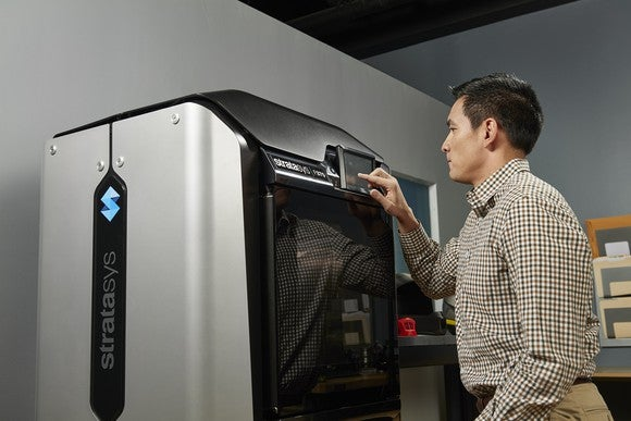 Worker operating a 3D printing machine.