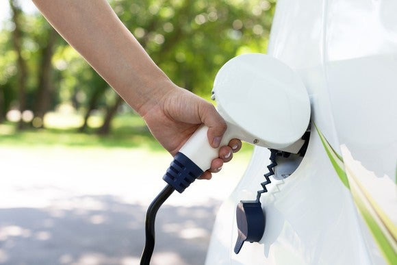 A person charging a white electric vehicle.
