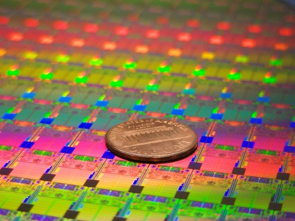 A wafer of semiconductor chips with a penny on top.