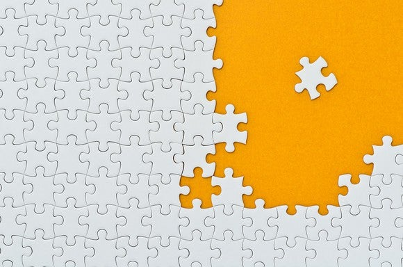 Photo of white puzzle pieces on orange background.