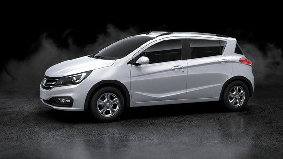 A white Baojun 310 hatchback against a black background.