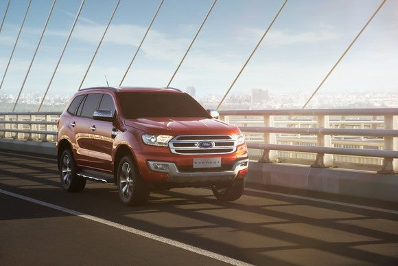 A red Ford Everest is shown driving across a bridge.