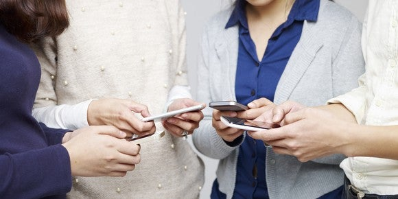 A group of people stand in a circle, all typing on their smart phones.