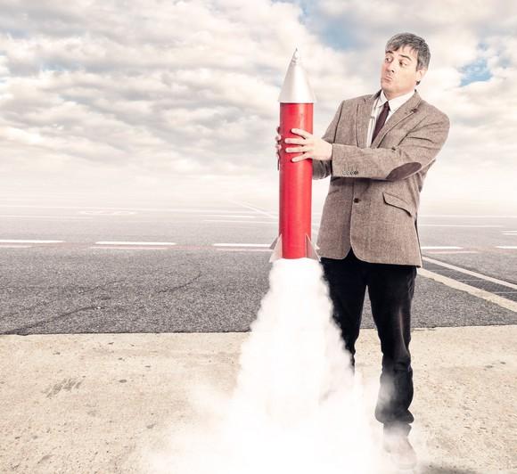 Man holding toy rocket, looking surprised as it starts to take off.