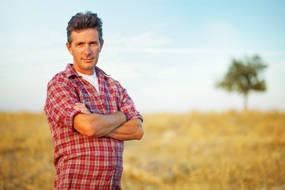 A farmer standing in a field with a rural background.