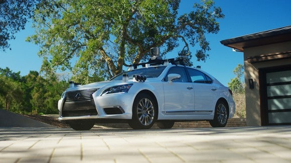 A white Lexus sedan with self-driving sensors in a suburban driveway.