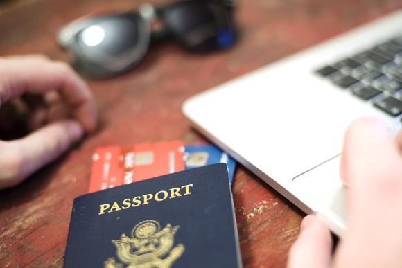 Passport on desk using a laptop