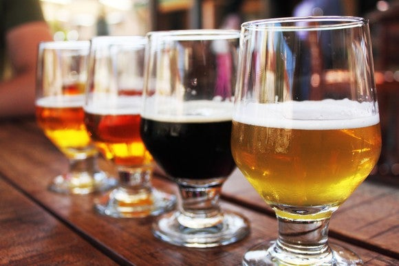 A row of draft beer, poured in glasses, on a bar top.