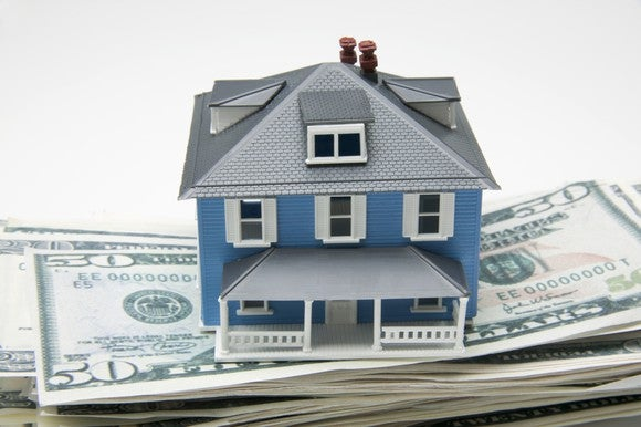 Model of house sitting on pile of cash.
