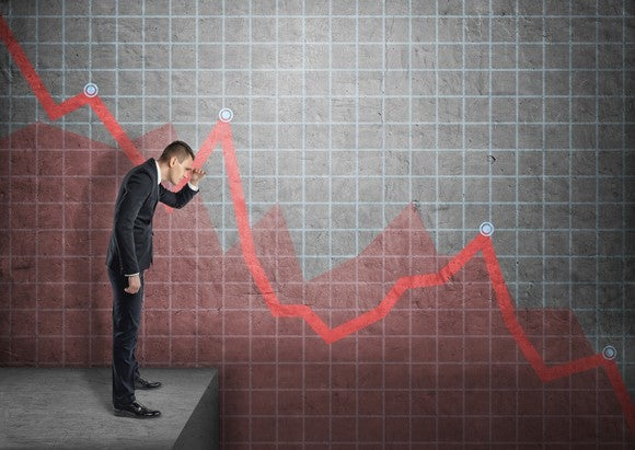 A businessman looking down a bar chart showing stock losses.