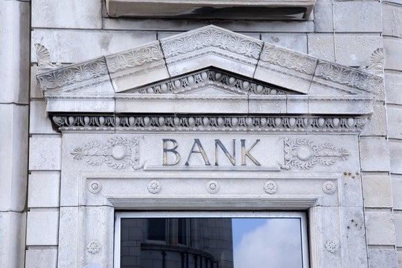 "Front door of a bank with the word ""bank"" above the entrance."