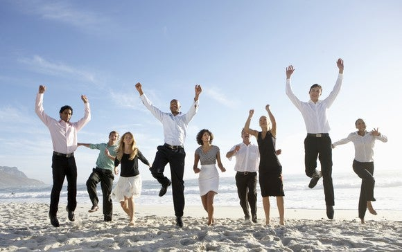 Businessmen and women jump for joy on a beach.