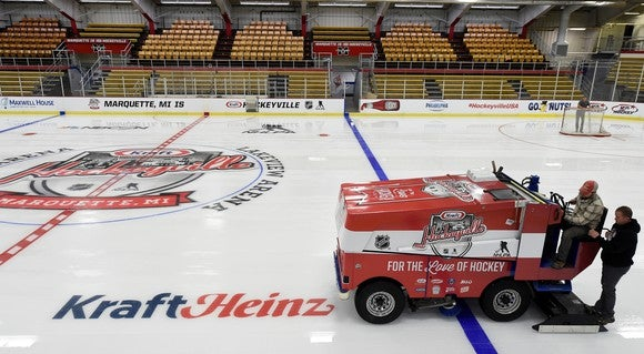 Zamboni on hockey rink with Kraft Heinz logo on it.