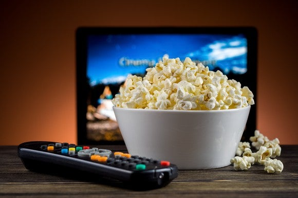 A bowl of popcorn and a TV remote in front of a TV.