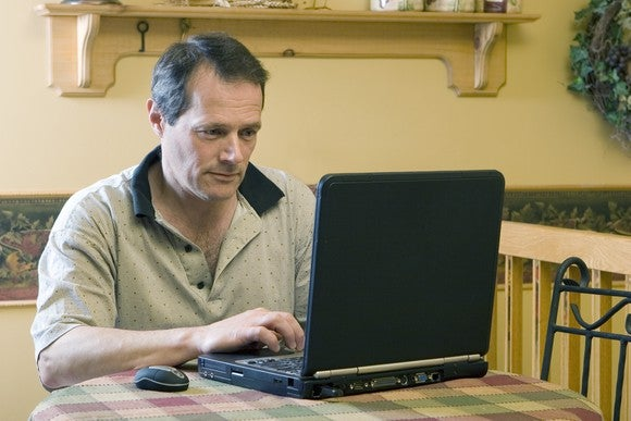 Older man working on laptop from home