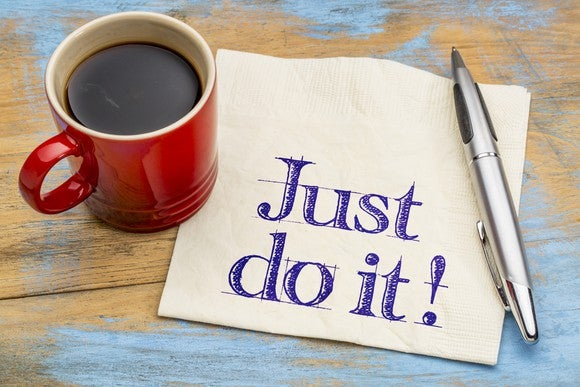 """Just do it"" printed on a white napkin next to a red mug of coffee."
