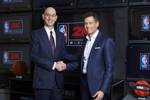 "Take-Two CEO Strauss Zelnick shakes hands with NBA Commissioner Adam Silver in front of a screen that says ""NBA 2K."""