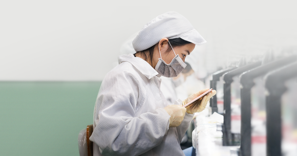 A worker assembles parts of an apple product.