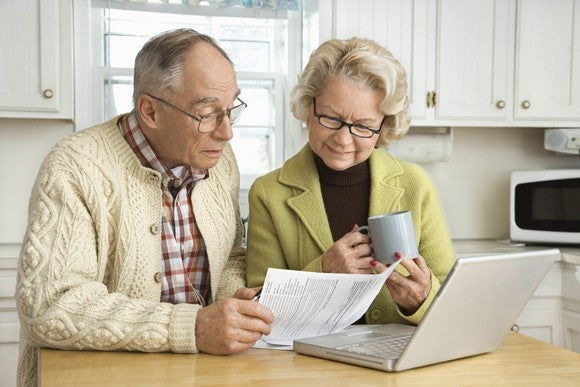 Older couple looking over financial paperwork.